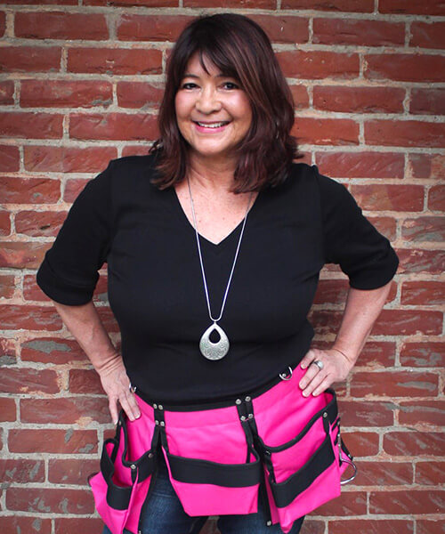Shot of Rose Tafoya smiling with a pink tool belt
